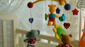 M?vil del beb? con diversos juguetes bajo la forma de animales y estrellas, sobre la cama de beb? almacen de metraje de vídeo