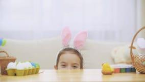Mała bawić się dziewczyna z królików ucho na jego głowie chuje pod drewnianym stołem Wielkanocne dekoracje, pełno Dziewczyna jest zbiory