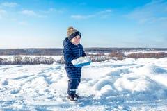 Mała chłopiec 3-5 lat w zimie w naturze, szczęśliwy ono uśmiecha się, chodzi z łopatą w rękach śnieg i obrazy stock