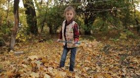 Mała dziewczynka angażuje w czyścić ulistnienie który spadał od drzew Dziewczyny grabienie opuszcza kolor żółtego zbiory