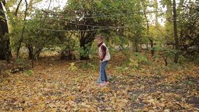 Mała dziewczynka angażuje w czyścić ulistnienie który spadał od drzew Dziewczyny grabienie opuszcza kolor żółtego zdjęcie wideo