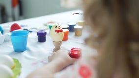 Mała dziewczynka ma zabawę podczas gdy malujący Easter jajko zbiory wideo