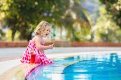 Mała dziewczynka pije sok przy pływackim basenem fotografia stock