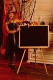 Mała dziewczynka w czarownika kapeluszowym punkcie przy ogłoszenie deską na Halloween Mała dziewczynka w czarownika kontuszu z sz zdjęcia stock