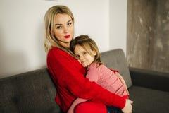 Mała dziewczynka w czerwonych rajstopy z mamą w czerwonym pulowerze szczęśliwy dom rodzinny Córka ściska jej matki obraz stock