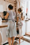 Mała dziewczynka zostaje na stolec obok jej matki gotuje bliny dla śniadania w małej wygodnej kuchni obraz royalty free