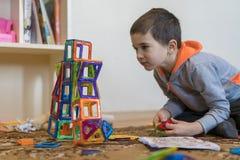 Mała uśmiechnięta chłopiec bawić się z magnesową konstruktor zabawką Chłopiec bawić się intelektualista zabawki zdjęcia royalty free