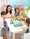 Małe dziecko sztuka z różnymi zabawkami z nauczycielem w daycare Dzieciaki buduje kolorów bloki Edukacyjne zabawki dla zdjęcia stock