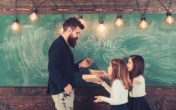 Małe dziewczynki słuchają brodaty mężczyzna przy zarządem szkołym Nauczyciel pisze z kredą na chalkboard Adiunkt uczy dzieci fotografia stock