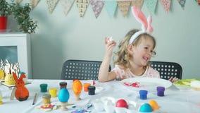 Małej dziewczynki łasowania Easter obrany jajko i ono uśmiecha się zdjęcie wideo