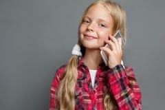 Małej dziewczynki pozycja odizolowywająca na popielaty opowiadać na smartphone przyglądającej kamerze radosnej w górę zdjęcie royalty free