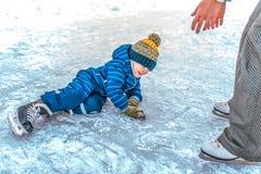 Mały chłopiec 2-5 lat, spadał na lodzie w zimy jazdie na łyżwach Mama podnosi jej syna szczęśliwy uśmiech Uczenie łyżwiarstwo obraz stock