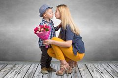 Mały syn daje jego ukochany matce pięknemu bukietowi różowe róże i całuje mum Wiosna, kobieta dzień, matka dzień obraz royalty free