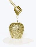 Maçã brilhante do ouro com gota do mel no dipper Fotos de Stock