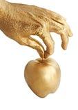 Maçã da terra arrendada da mão do ouro Imagens de Stock Royalty Free