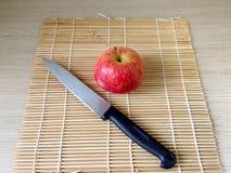 Maçã e faca vermelhas no close up de madeira da tabela Imagem de Stock