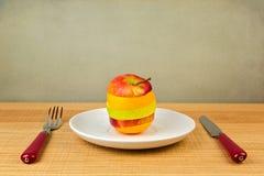 Maçã e laranja cortadas na placa Conceito da dieta saudável Fotos de Stock