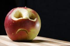 Maçã enfrentada triste na placa de madeira Imagem de Stock