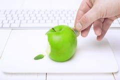 Maçã fresca como o mealheiro e a mão com moeda Conceito no estilo: Investimento na informática  Fundo branco Imagem de Stock Royalty Free