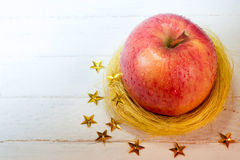 Maçã fresca no ninho dourado e estrelas no fundo de madeira branco imagens de stock royalty free