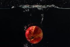 Maçã fresca vermelha que cai na água com respingo Fotografia de Stock Royalty Free