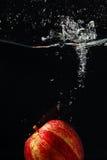 Maçã fresca vermelha que cai na água com respingo fotografia de stock