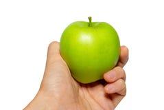 Maçã saboroso verde em uma mão com fundo branco foto de stock royalty free