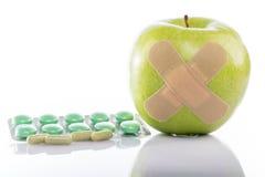 Maçã verde com um curativo e os comprimidos dos varios fotografia de stock