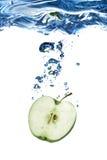 A maçã verde deixou cair na água imagem de stock royalty free
