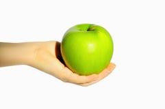 Maçã verde em uma mão Foto de Stock