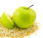 A maçã verde fresca com um segmento na aveia lasc. Imagens de Stock