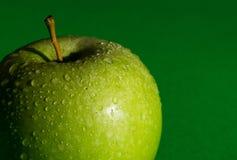 Maçã verde fresca vista parcialmente com gotas da água no fundo verde imagens de stock royalty free