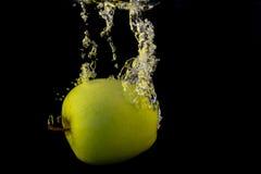 Maçã verde no respingo amarelo isolado no fundo preto Foto de Stock