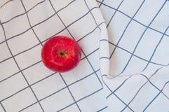 Maçã vermelha bonita na toalha dobrada branca imagem de stock royalty free
