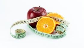 Maçã vermelha com duas metades das laranjas envolvidas com fita de medição imagem de stock royalty free