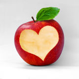 Maçã vermelha com um entalhe dado forma coração. Imagens de Stock