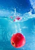 A maçã vermelha deixou cair na água com respingo Imagens de Stock Royalty Free
