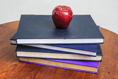 Maçã vermelha e livros velhos na tabela de madeira Imagem de Stock Royalty Free