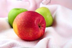 Maçã vermelha e verde no pano cor-de-rosa Foto de Stock