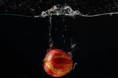 Maçã vermelha madura que cai na água com respingo imagens de stock royalty free