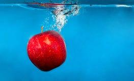 Maçã vermelha na água com respingo e gotas sobre o azul Fotos de Stock Royalty Free