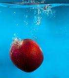 Maçã vermelha na água com respingo e gotas sobre o azul Fotografia de Stock