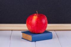 Maçã vermelha no mini livro velho contra o quadro-negro fotografia de stock royalty free