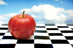 Maçã vermelha no tabuleiro de xadrez imagem de stock