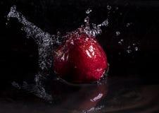 Maçã vermelha que cai na água com respingo no fundo preto imagens de stock royalty free