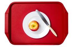 maçã Vermelho-amarela com uma faca em uma placa branca contra o vermelho Fotografia de Stock Royalty Free