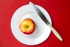maçã Vermelho-amarela com uma faca em uma placa branca contra o vermelho Fotografia de Stock