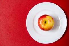 maçã Vermelho-amarela em uma placa branca contra o fundo vermelho Foto de Stock