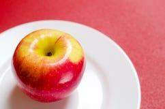 maçã Vermelho-amarela em uma placa branca contra o fundo vermelho Fotos de Stock