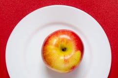 maçã Vermelho-amarela em uma placa branca contra o fundo vermelho Imagens de Stock